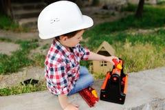 白色建筑盔甲的男婴 免版税库存照片