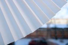 白色弯曲了布料、纸与三角小条和小孔,毛孔半圆爱好者在窗口的背景中 库存照片