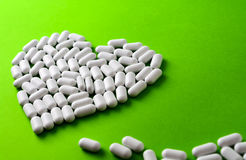 白色心脏由药片做成在绿色背景 库存图片