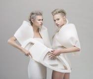 白色成套装备的两名未来派白肤金发的妇女 免版税库存照片