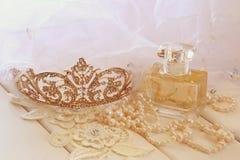 白色成珠状项链、金刚石冠状头饰和香水瓶 免版税库存图片