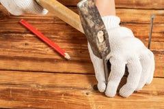 白色手套的一个人锤击木表面上的一个钉子 库存照片