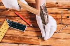 白色手套的一个人锤击木表面上的一个钉子 免版税图库摄影