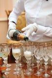 白色手套的侍者倒了香槟 免版税库存照片