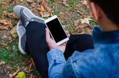 白色手机在手中坐和看电话的一个年轻行家商人 图库摄影