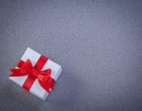白色把与红色被栓的弓的礼物装箱灰色表面假日c 免版税库存图片