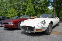 白色捷豹汽车E XKE系列3和在游行汽车品牌捷豹汽车的红色捷豹汽车XJ-S (XJS) 芬兰土尔库 库存照片