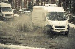 白色搬运车在大水坑乘坐在多雪的天 在一Ma的雨夹雪飞溅 库存照片