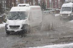白色搬运车在大水坑乘坐在多雪的天 库存图片