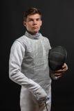白色操刀的服装的英俊的年轻男性击剑者 免版税库存照片