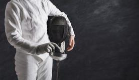 白色操刀的衣服的女性击剑者在黑背景 库存图片