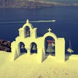 白色教会钟楼在蓝色海,圣托里尼,希腊上的 免版税库存图片