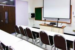 白色教室是现在可以得到的与学生书桌和椅子 库存照片