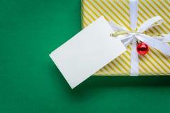 白色文本标签和礼物盒的顶视图嘲笑在绿色ta 免版税图库摄影