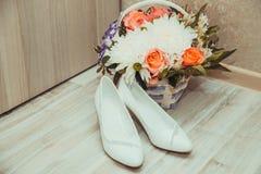 白色新娘婚礼鞋子和花束在篮子 库存照片
