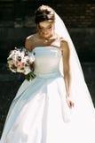 白色新娘礼服的新娘有花束的 库存照片