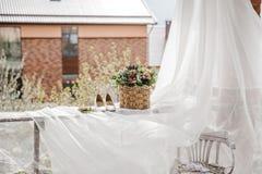 白色新娘鞋子和花在篮子 免版税库存照片