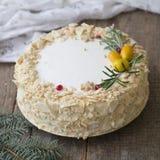 白色新年或圣诞节蛋糕拿破仑,装饰用迷迭香金桔、在一张木桌上的小树枝和蔓越桔 库存图片