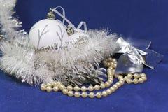 白色新年球和闪亮金属片在蓝色背景 库存照片