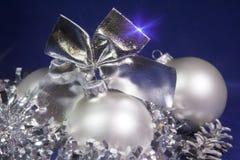 白色新年球和闪亮金属片在蓝色背景 免版税库存照片