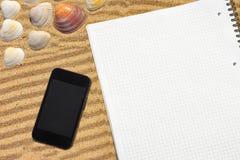 白色方格的笔记薄和智能手机在海滩 库存照片