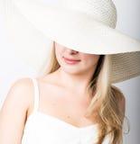 白色无袖衫和一大白色帽子微笑的美丽的滑稽的年轻白肤金发的妇女 一部分的面孔包括帽子 库存图片