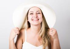 白色无袖衫和一大白色帽子微笑的美丽的滑稽的年轻白肤金发的妇女 免版税库存照片