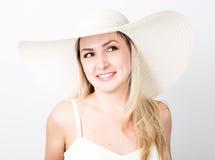 白色无袖衫和一大白色帽子微笑的美丽的滑稽的年轻白肤金发的妇女 库存照片
