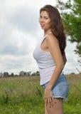 白色无袖衫和牛仔布短裤的美丽的两种人种的妇女 免版税库存图片