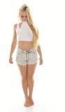 白色无袖衫和短裤的性感的年轻白肤金发的妇女 库存照片