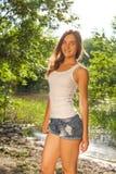 白色无袖衫的美丽的年轻白肤金发的妇女和 免版税库存照片
