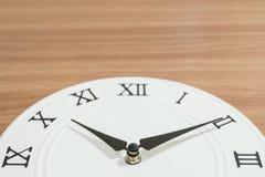 白色时钟的特写镜头零件为在木书桌被构造的背景的十过去十个o `时钟装饰与拷贝空间 免版税图库摄影