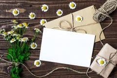 白色春黄菊花和空白的白色贺卡花束与礼物盒 库存图片