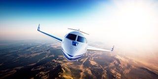 白色普通飞行在山的设计私人喷气式飞机现实照片  空的蓝天和太阳在背景 库存图片