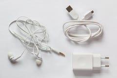 白色智能手机充电器、USB缆绳和白色耳机在白色背景 库存图片