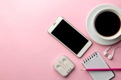 白色智能手机和一杯咖啡和办公用品在明亮的桃红色背景 在视图之上 免版税库存照片