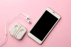 白色智能手机和耳机在明亮的桃红色背景 在视图之上 免版税图库摄影