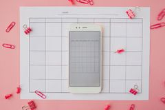白色智能手机在纸日历说谎 o 免版税库存照片