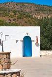 白色有一个蓝色门、一口石头井和一个雕象的黏土希腊房子在入口 免版税库存图片