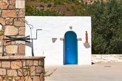 白色有一个蓝色门的黏土希腊房子和在入口的一个雕象 库存照片