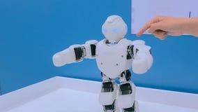 白色有人的特点的机器人跳舞 图库摄影