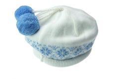 白色有大型机关炮的被编织的冬天羊毛帽子 免版税图库摄影