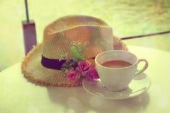 白色有葡萄酒样式的杯子热的茶和草帽 库存照片