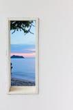 白色木墙壁窗口有日落海海滩视图 免版税库存照片
