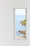 白色木墙壁窗口有海海滩视图 免版税库存图片