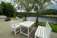 白色木桌和长凳在湖边在好的公园 免版税库存图片