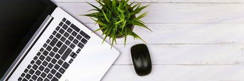 白色木桌的工作场所与拷贝空间 膝上型计算机,老鼠,电话,在罐的花 r 黑板顶视图  免版税库存图片