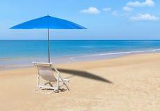 白色木海滩睡椅和蓝色遮阳伞在热带海滩 免版税库存照片