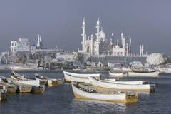 白色木渔船行在口岸的一棵小植物中站立,以白色清真寺和白色树的方式,科瓦兰,南Ind 免版税图库摄影