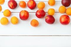 白色木背景用水多的橙色杏子和明亮的新鲜的红色necratins和桃子 免版税库存图片